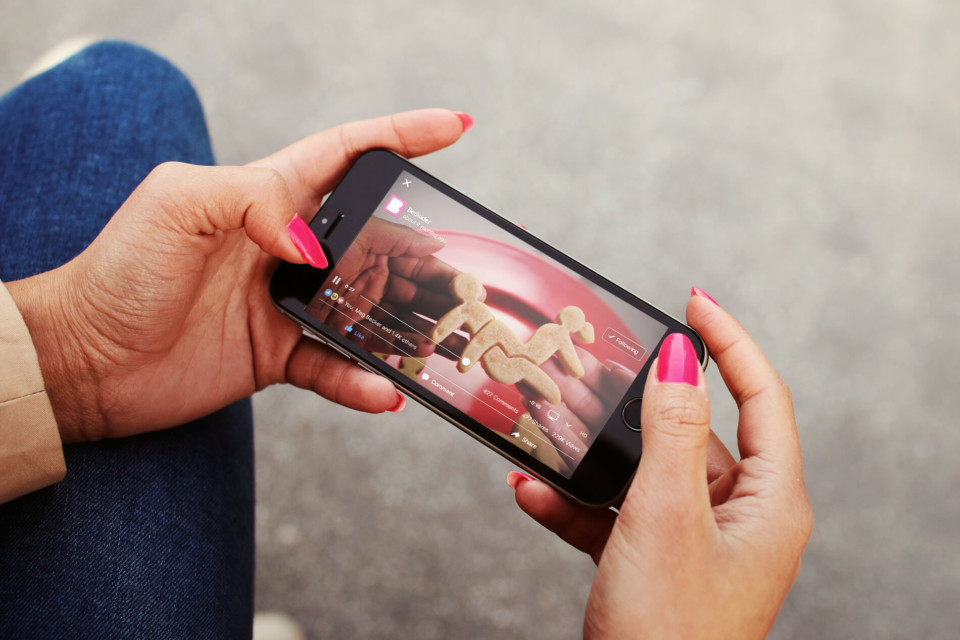 woman watches a video on a mobile phone